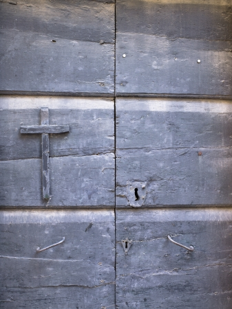 Old wooden door with religious cross in a close-up image. Stock Photo - 17486702