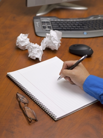 Close-up shot of a person writing on spiral notepad on wooden desk with spectacles and crushed papers. photo