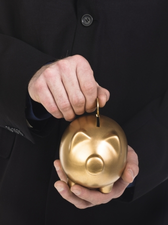 coins shot in golden color: Close-up shot of a businessman putting gold coin in golden piggy bank. Model: WInter Bourne Stock Photo