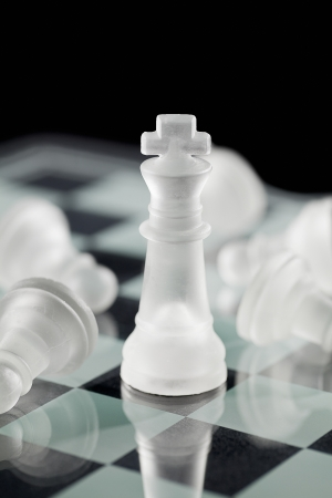 Close-up shot of chess king standing amid fallen chess pawn on board photo