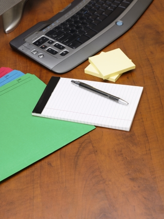 Close-up shot of pen and notepad with adhesive note and keyboard on wooden office desk. Stock Photo - 17494637
