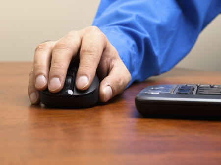 Detailed shot of human hand holding optical mouse on wooden desk. Stock Photo - 17494832