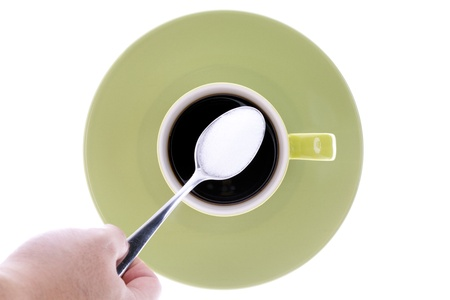 Close-up top view of human hand holding teaspoon full of sugar over cup of black coffee with saucer. photo