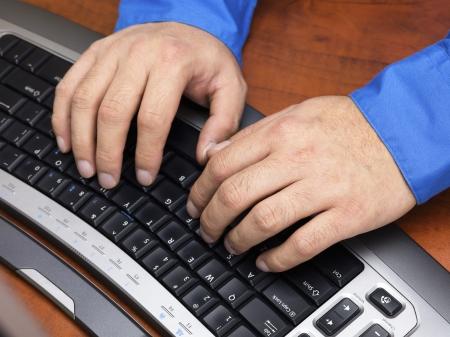 Detailed shot of a man typing on black keyboard. Stock Photo - 17494297