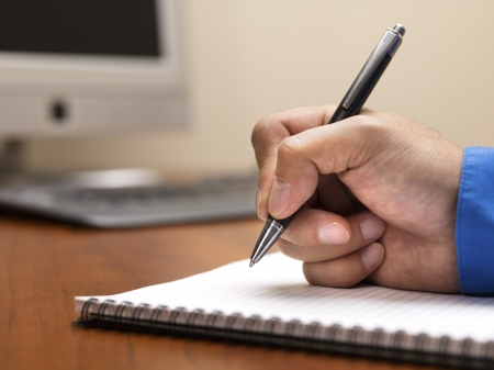Detailed shot of human hand writing with pen on spiral writing pad on wooden office desk. Stock Photo - 17496264