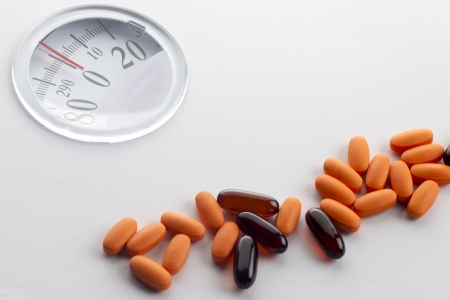 heavy weight: Detailed shot of capsules on white weight scale machine.