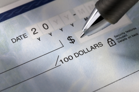 writing western: Detailed view of a check and a pen.