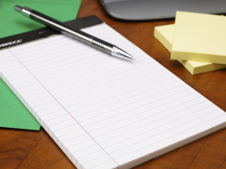 Detailed cropped shot of notepad and pen on wooden office desk. Stock Photo - 17496235