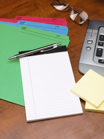 Detailed cropped shot of a blank notepad with pen and files on wooden desk. photo