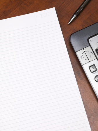 Close-up cropped shot of a blank notepad with keyboard and pen on wooden desk. Stock Photo - 17494853