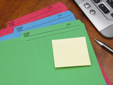 Close-up cropped shot of colorful files and adhesive note with pen and keyboard on wooden desk. photo