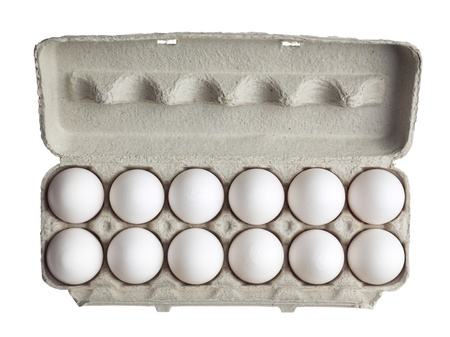 Close-up of dozen of eggs in carton box isolated over white background photo