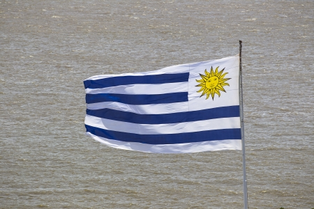 Flag of Uruguay waving in water surface background Imagens