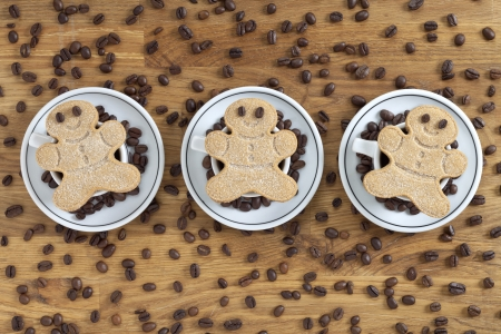 Gingerbread men cookies with coffee drink and beans on wood photo