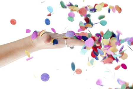 Close-up image of human hand touching decorative confetti falling against white background. Stock Photo - 17496290
