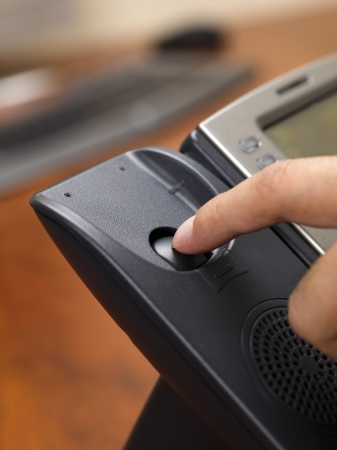 disconnecting: Close-up shot of human finger disconnecting black landline phone. Stock Photo