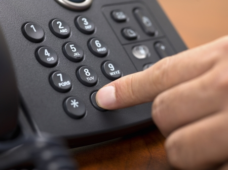 phone button: Close-up shot of human hand dialing number on black landline phone.