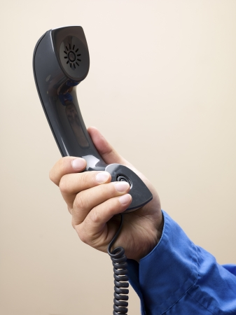 Close-up shot of human hand holding black telephone receiver over plain background. photo