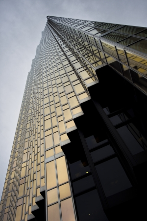 property development: Low angle view of a elegant tall corporate building against cloudy sky.