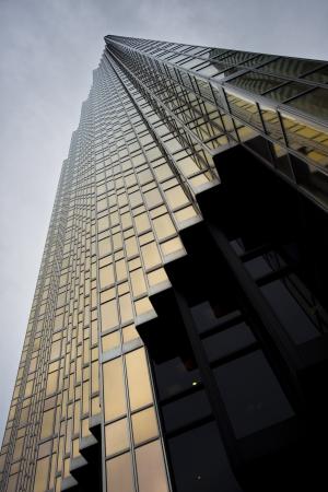 edificio corporativo: �ngulo de visi�n baja de un elegante edificio alto corporativo contra el cielo nublado. Foto de archivo