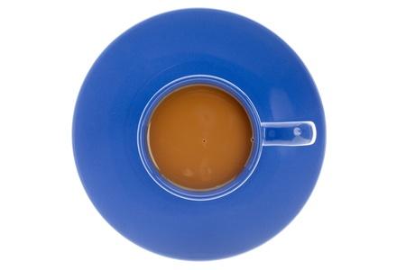 tomando refresco: Close-up vista desde arriba de una taza de caf� con plato azul sobre fondo azul.