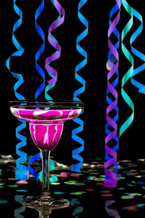 Close-up shot of martini with pink drink and streamers and colorful confetti over dark background. Stock Photo - 17496198