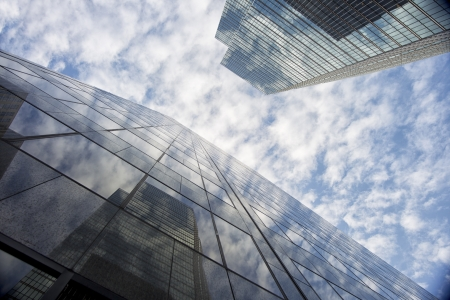 Low angle shot of reflection on tall commercial buildings against cloudy sky.
