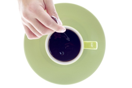 Close-up top view of a person stirring coffee over white background. photo