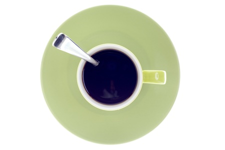 Close-up top view of a green coffee cup and saucer with a teaspoon. photo