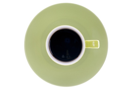 Close-up top view of green cup with black coffee with saucer over white background. photo
