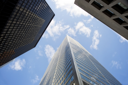 Low angle shot of tall office buildings against cloudy sky.