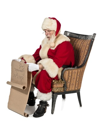 wish list: Santa clause reading Christmas wish list wearing a red costume while sitting on a chair