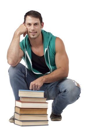 hooded vest: Portrait of a smiling man with books sitting on a white surface Stock Photo