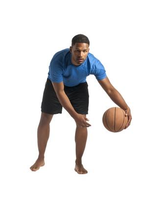 aieron: Ritratto di afro-americano uomo dribbling la palla sopra la superficie bianca