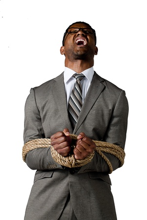 Portrait of an angry businessman with rope tied on his hand isolated on a white background photo