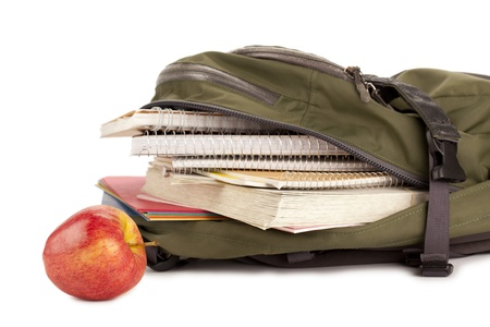 educational tools: Cropped image of a green school backpack with school supplies and apple on the side