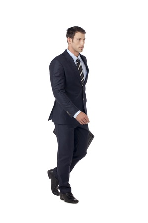 Portrait of an attractive businessman holding his briefcase while walking on a white surface