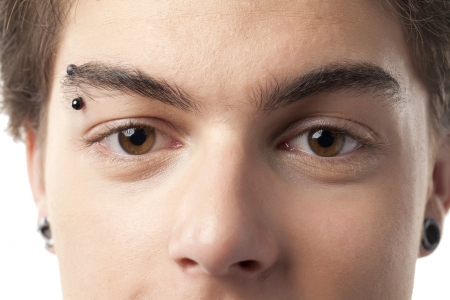 flesh: Beautiful eyes and nose of a man with eyebrow piercing and flesh ear tunnel