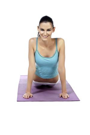 Portrait of beautiful lady practicing yoga exercise against white background