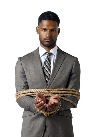 tied knot: Portrait of serious businessman wrapped up with brown rope against white background