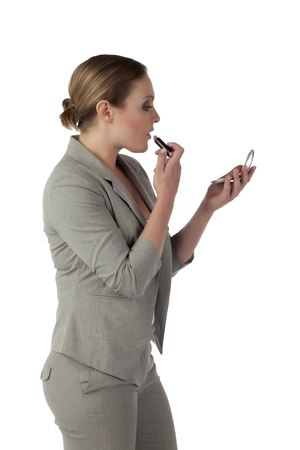 Portrait of businesswoman putting lipstick on her lips against white background photo