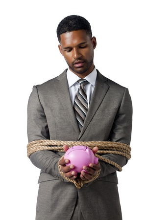 Business crisis concept represented by a tied businessman holding a piggy bank photo