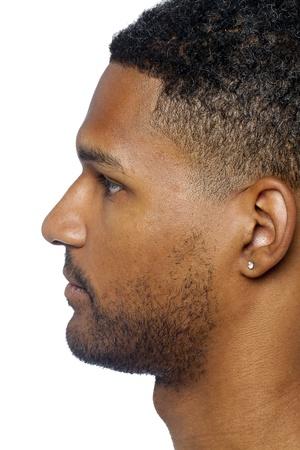 aieron: Uomo scuro con orecchio trafitto sulla vista laterale, isolato su una superficie bianca