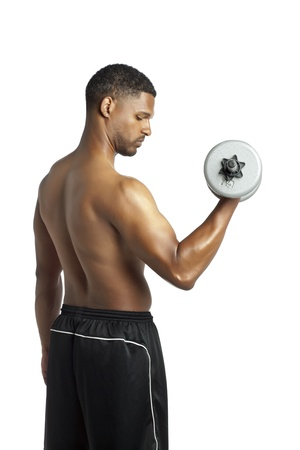 Side view of a fit muscular man with dumbbell exercising over the white surface