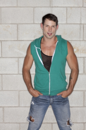 hooded vest: Handsome muscular man looking at the camera while hands on his pocket