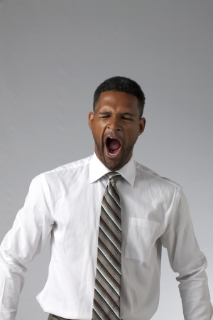 aieron: Portrait of black businesman yawning against a grey background Stock Photo