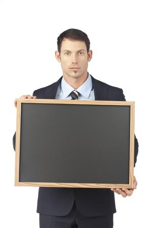 Serious businessman holding a blackboard Stock Photo - 17520756