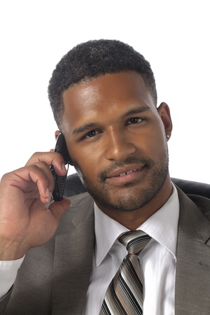Businessman looking at the camera while listening to someone via cellular phone photo