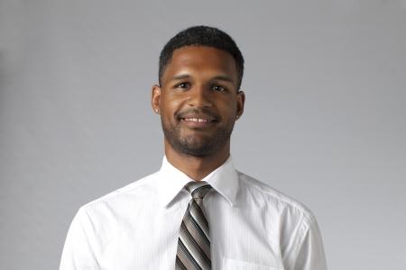 aieron: Close-up immagine di un giovane uomo d'affari sorridente contro lo sfondo grigio