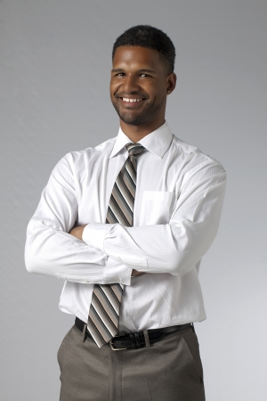 aieron: Portrait of a businessman with crossed arm smiling over the gray background Stock Photo